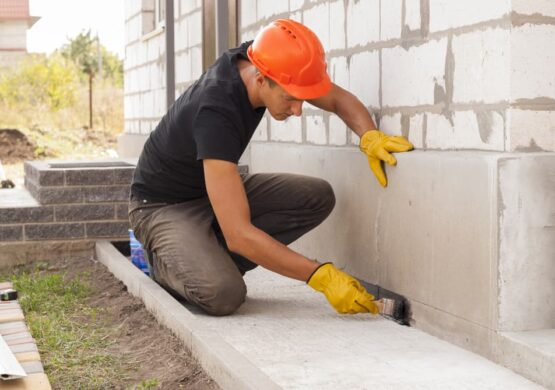 Man working with concrete outside wearing protective construction gear